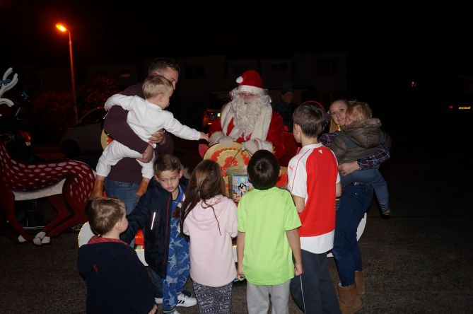 Santa greeting local children on his route