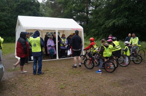 Marshals and early arriving cyclists shelter from the shower