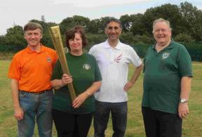 SADSAD Games - Lions President Marilyn holds and Olympic torch with the local torch bearer, Lion Iain and Lion Phil